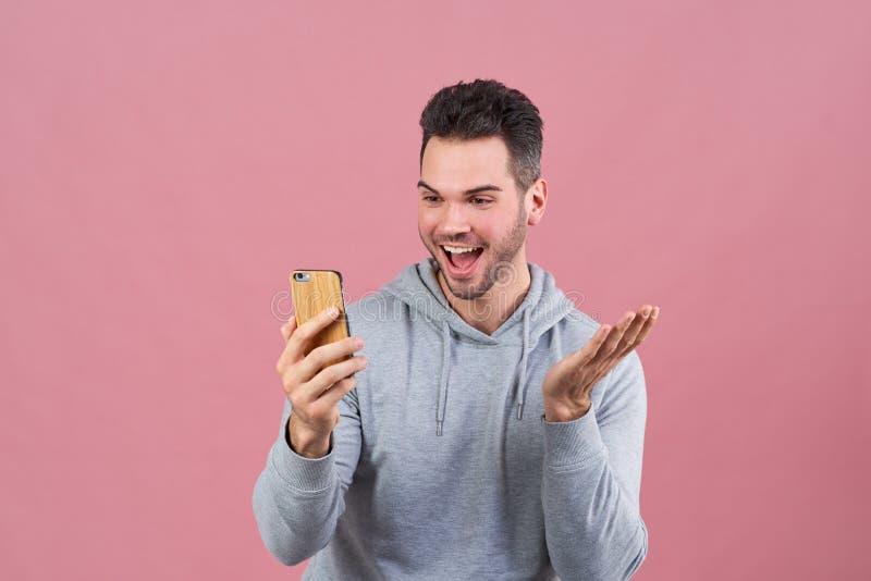 De sportieve jonge kerel is opgewekt over nieuwe mobiele app en enthousiast glimlachend en het golven van zijn handen bekijkend d royalty-vrije stock foto's