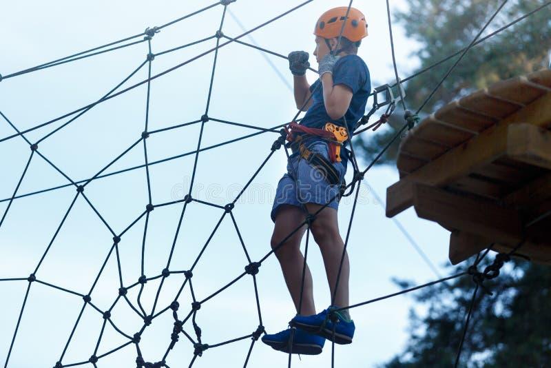 De sportieve, jonge, leuke jongen in witte t-shirt brengt zijn tijd in het park van de avonturenkabel in helm en veilig materiaal stock foto