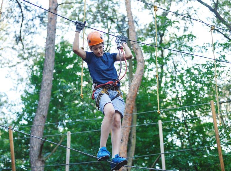 De sportieve, jonge, leuke jongen in witte t-shirt brengt zijn tijd in het park van de avonturenkabel in helm en veilig materiaal stock afbeeldingen