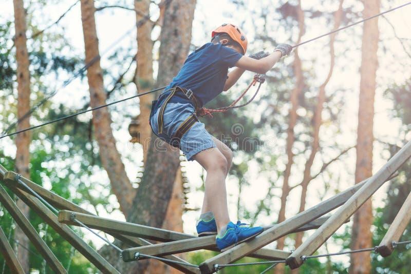 De sportieve, jonge, leuke jongen in witte t-shirt brengt zijn tijd in het park van de avonturenkabel in helm en veilig materiaal royalty-vrije stock foto's