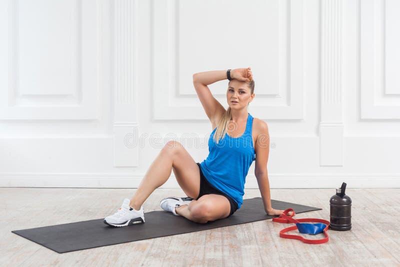 De sportieve mooie jonge atletische blondevrouw in zwarte borrels en de blauwe bovenkant worden gezweet en hebben een rust na har stock fotografie