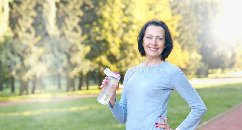 De sportieve rijpe fles van de vrouwengreep met water openlucht op zonnige dag in het park royalty-vrije stock afbeelding