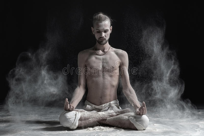 De sportieve rustige jonge mens die zitting in met de benen over elkaar yogalotusbloem mediteren stelt, Padmasana met palmen in m stock foto's