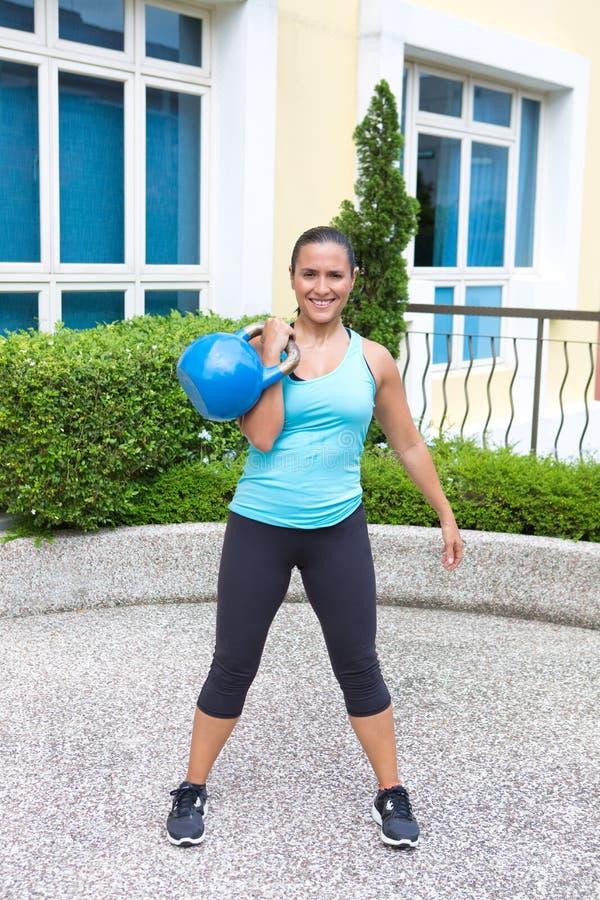 De sportieve Spaanse vrouw in blauwe opleiding met kettlebell in schoon stelt stock afbeelding