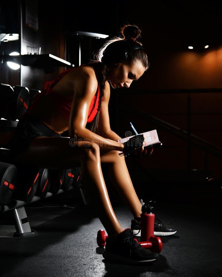 De sportieve trainer van de vrouwengeschiktheid schrijft resultaten in zuivel planningspraktijk neer Dieet en gewichtsverliesconc stock foto's