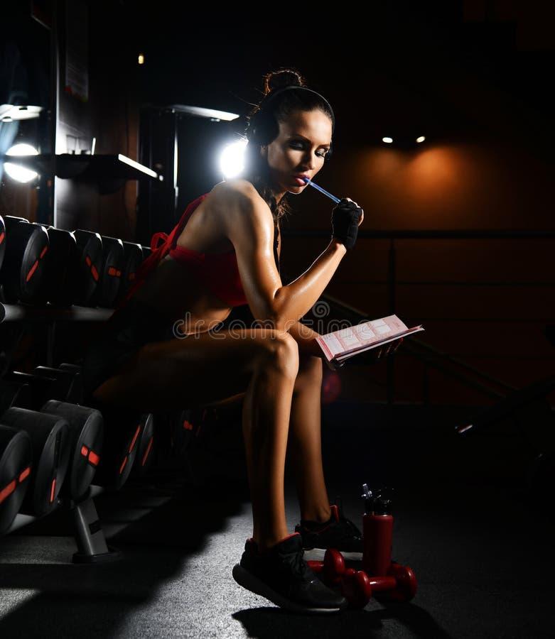De sportieve trainer van de vrouwengeschiktheid zit in gymnastiekzaal en denkt over oefeningenplan Dieet en gewichtsverliesconcep royalty-vrije stock foto's