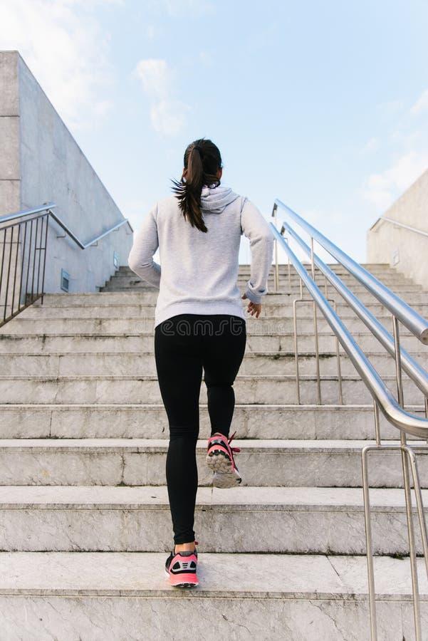 De sportieve vrouw die en treden in werking stellen beklimmen bekijkt terug royalty-vrije stock afbeelding