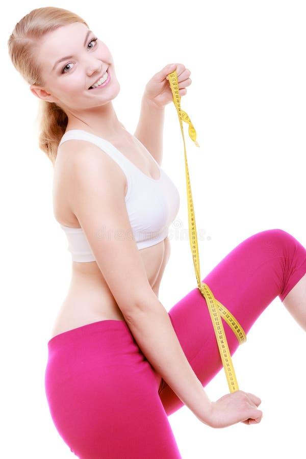 De sportieve vrouw die van het geschiktheidsmeisje haar geïsoleerde dij meten stock foto