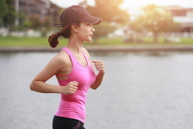 De sportieve vrouwelijke oefening van de joggerochtend op kust in het park stock afbeelding