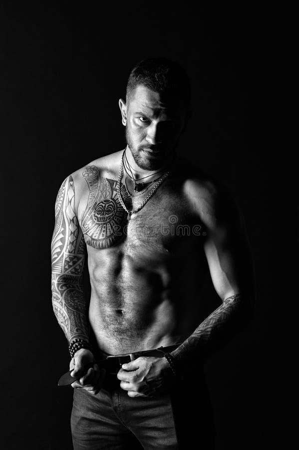 De sportman met zes pakt en ab in Het leerriem van de mannequingesp in jeans Mens met tatoegeringsontwerp op huid Gebaarde mens royalty-vrije stock afbeeldingen
