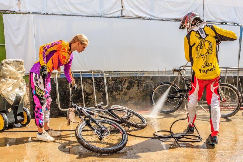 De sportmannenfietsers reinigen fietsen met de uitrusting van de hoge drukwas Berg het biking in het park van de terreinfiets Fie stock fotografie