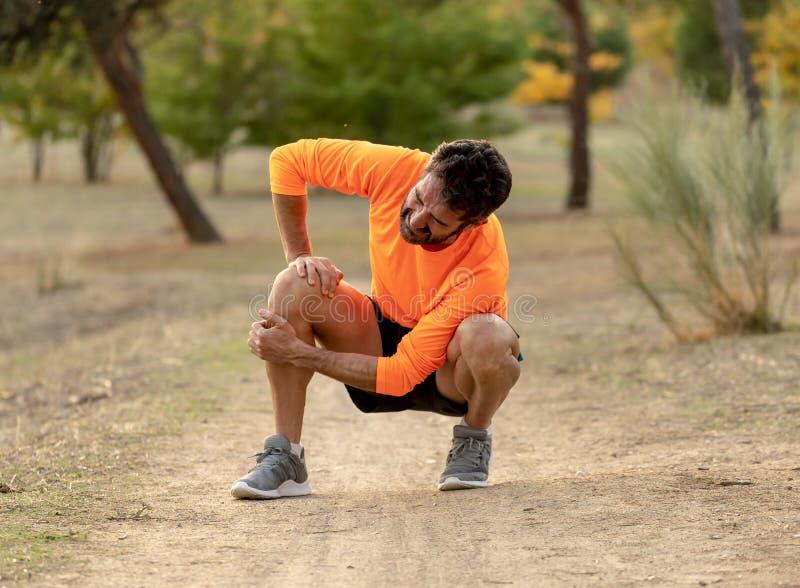 De sportmens verwondde toen het uitoefenen of het lopen houdend zijn knie gillend in pijn royalty-vrije stock foto