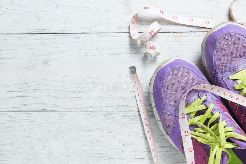 De sportvlakte legt purpere schoenen en het meten van band op witte houten achtergrond met copyspace voor uw tekst Concepten gezo stock foto