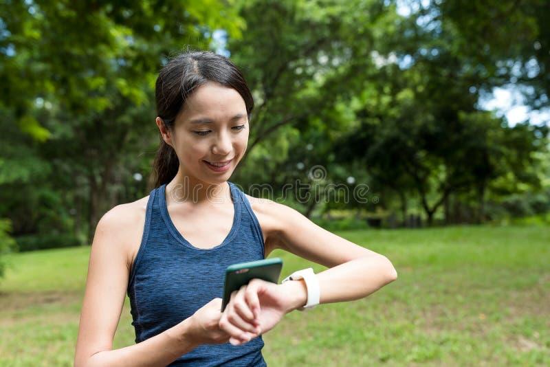 De sportvrouw die slim horloge met behulp van verbindt met mobiele telefoon stock fotografie