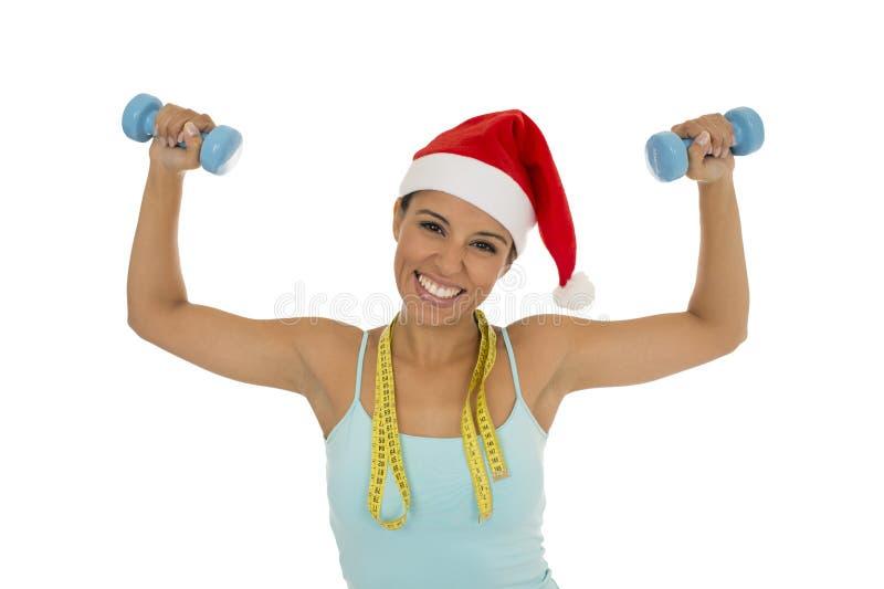 De sportvrouw in van de Kerstmishoed van de Kerstman de holdingsmaatregel bindt vast royalty-vrije stock foto's