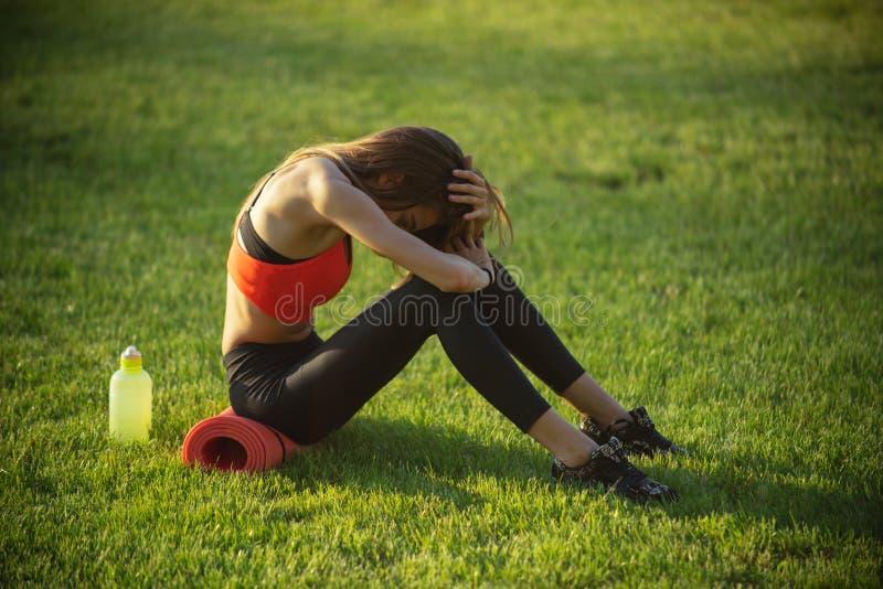 De sportvrouw zit op groen gras met gymnastiekmateriaal op de zomer royalty-vrije stock foto's