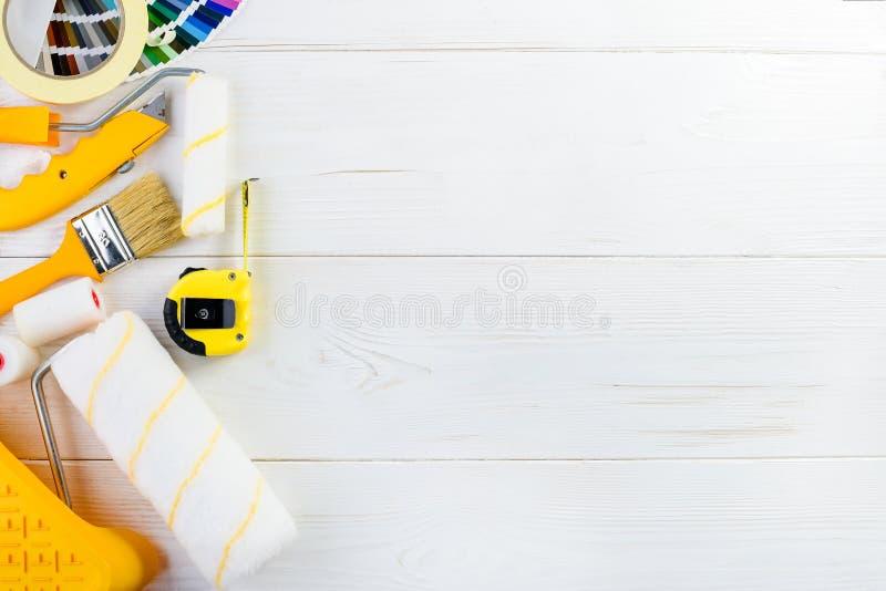 De spot omhoog van de catalogus van kleurensteekproeven, de borstel, de roulette en de verf rollen stock afbeelding