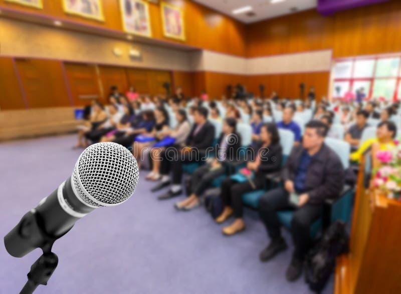 De spreker van de microfoonstem met publiek of studenten in seminarie c stock foto