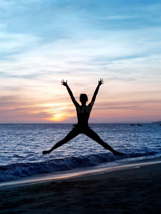 De springende vrouw van het silhouet op het strand stock foto's