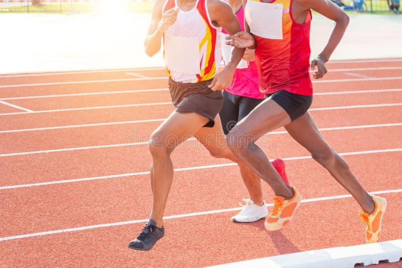 De sprint die van bewegingsatleten op renbaan in stadion lopen stock foto's