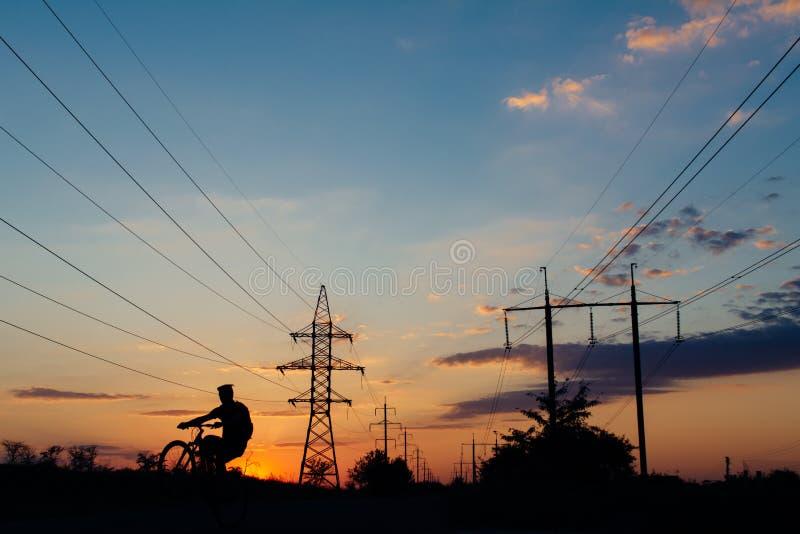 De sprong van de fietsruiter op de hemel van de fietszonsondergang betrekt de elektriciteit van machtslijnen stock foto