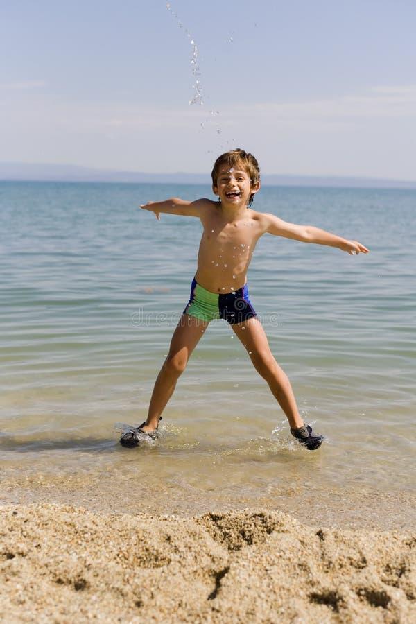 De sprong van het kind op zeekust stock fotografie