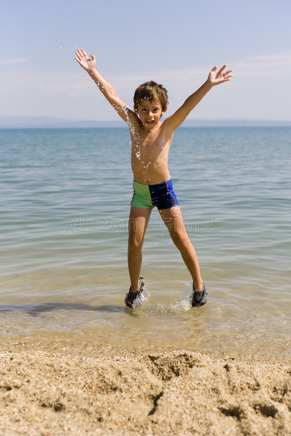 De sprong van het kind op zeekust royalty-vrije stock foto's