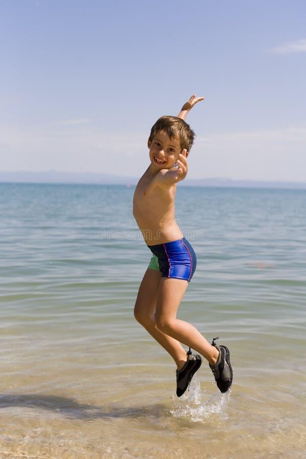 De sprong van het kind op zeekust royalty-vrije stock foto