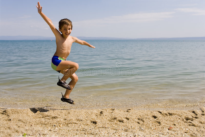 De sprong van het kind op zeekust royalty-vrije stock afbeelding