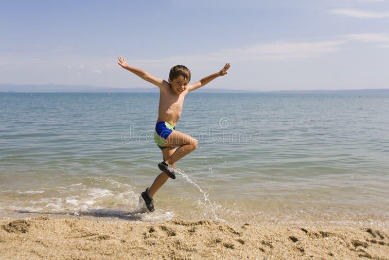 De sprong van het kind op zeekust royalty-vrije stock fotografie