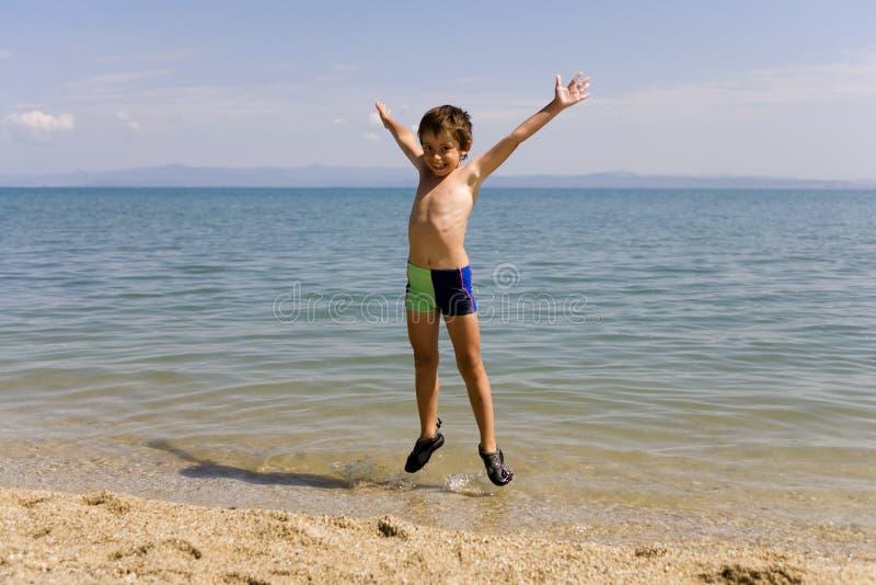 De sprong van het kind op zeekust royalty-vrije stock afbeeldingen