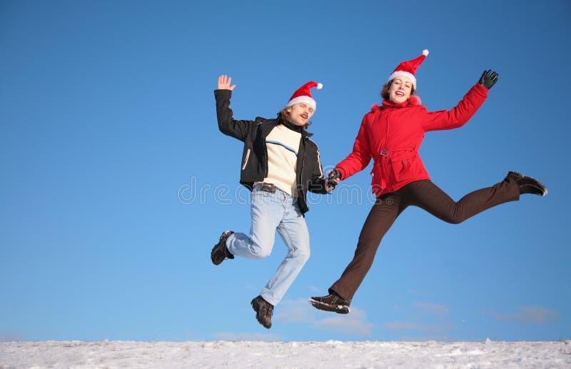 De sprong van het paar op sneeuw stock foto's