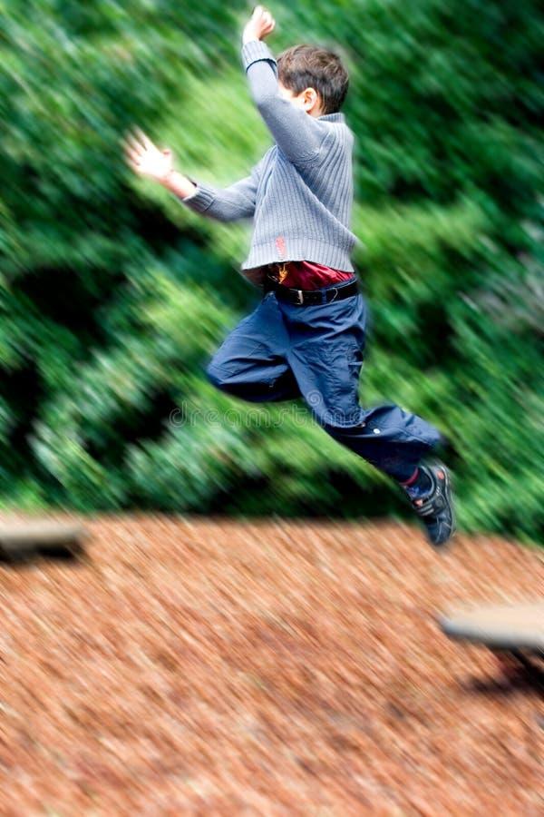 De sprongen van de jongen hoog in speelplaats stock fotografie