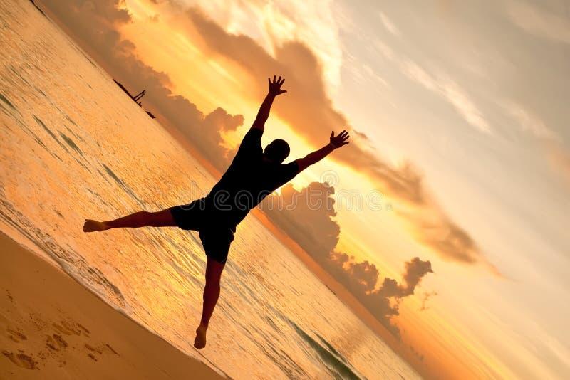 De sprongen van de mens voor zonsondergang op de oceaan stock fotografie