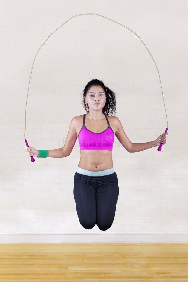 De sprongen van de vrouw met touwtjespringen royalty-vrije stock afbeelding