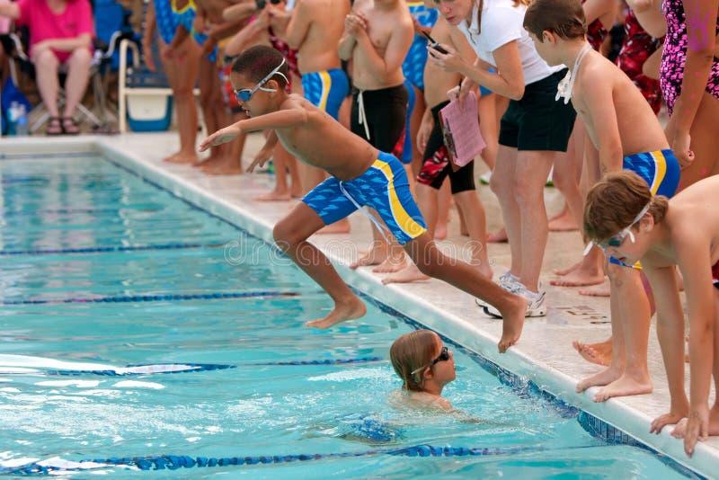 De Sprongen van de Zwemmer van het kind in Pool om de Race van het Relais te zwemmen royalty-vrije stock afbeelding