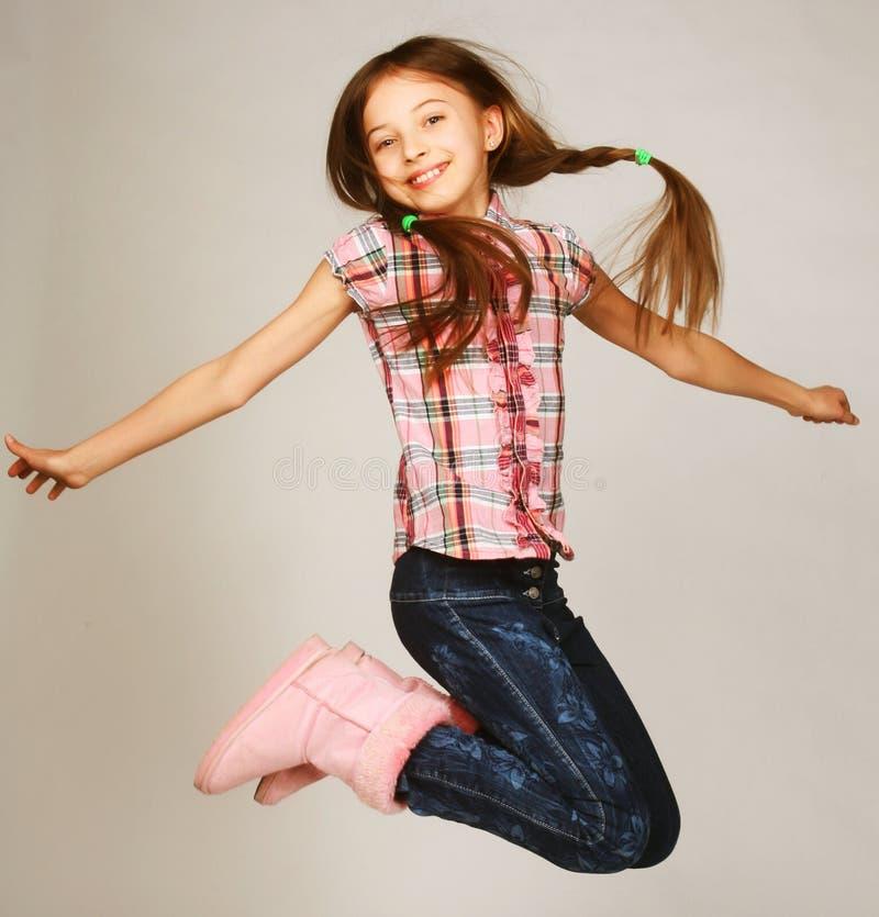 De sprongen van het meisje op een grijze achtergrond stock afbeeldingen
