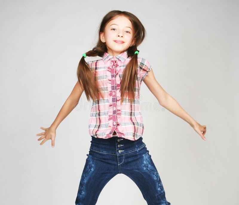 De sprongen van het meisje op een grijze achtergrond royalty-vrije stock afbeelding