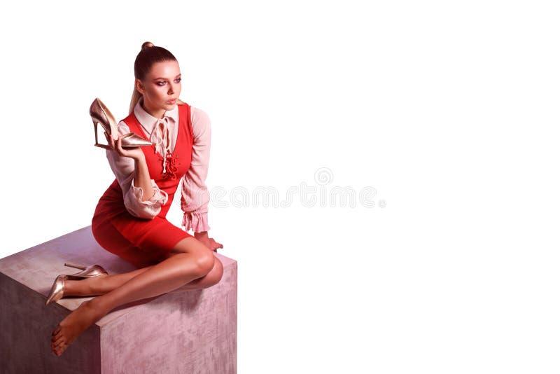De spruit van de manierstudio van stellende vrouw in rode kleding op grote kubus ho royalty-vrije stock foto