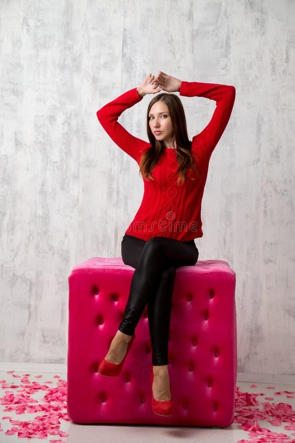 De spruit van de manierstudio van stellende vrouw in rode sweater stock afbeelding