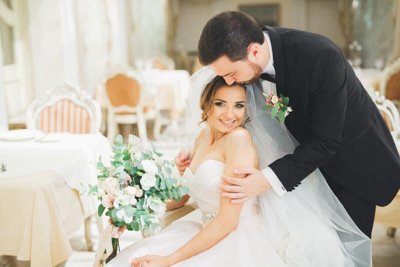 De spruit van de huwelijksfoto van jonggehuwdenpaar het stellen in een mooi hotel stock foto