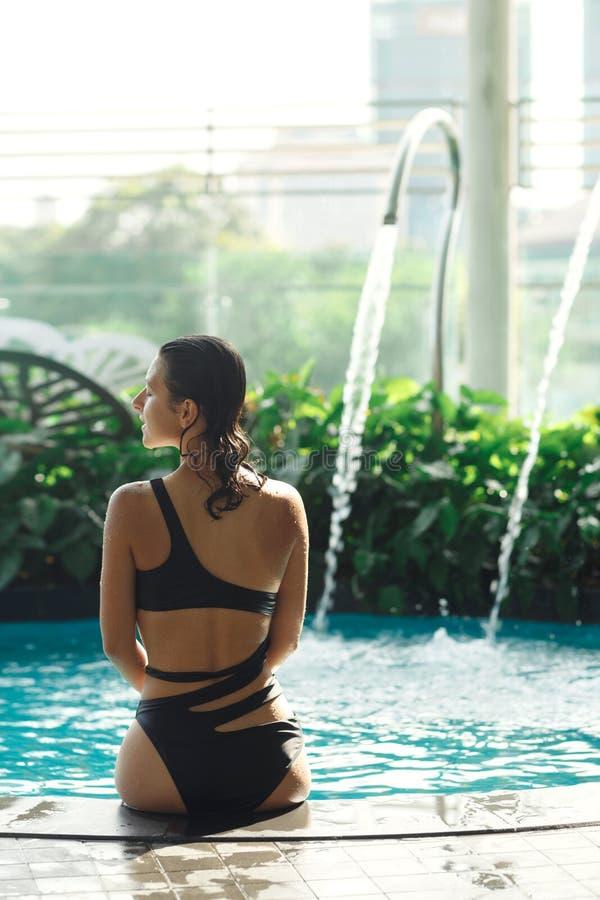De spruit van rug van sexy slank wijfje in zwempak zit op rand van zwembad tussen groene struiken op dak met stad scape stock foto