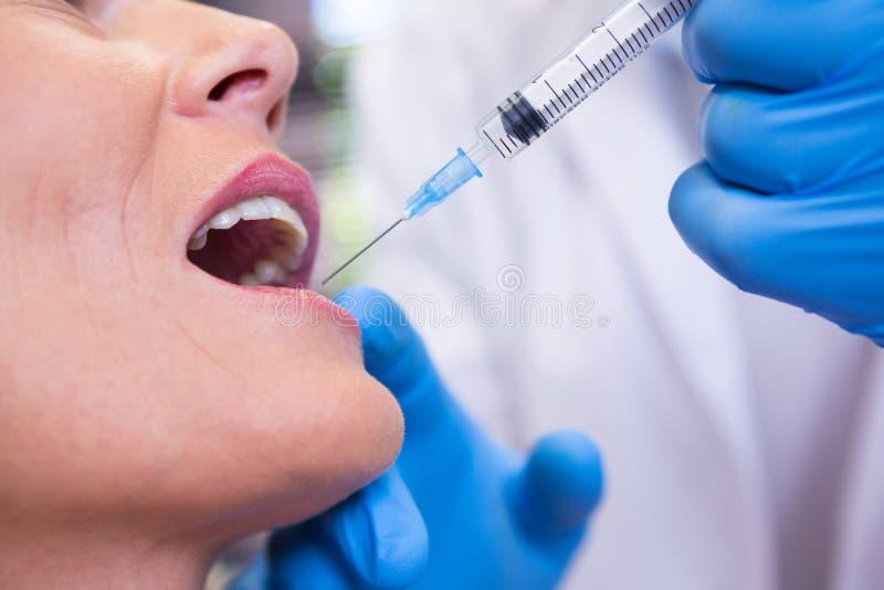 De spuit van de tandartsholding door patiënt bij medische kliniek royalty-vrije stock foto