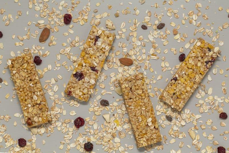De staaf van Granola De bar van graangewassengranola met noten, fruit en bessen op een grijze steenlijst Gezonde zoete dessertsna stock afbeeldingen
