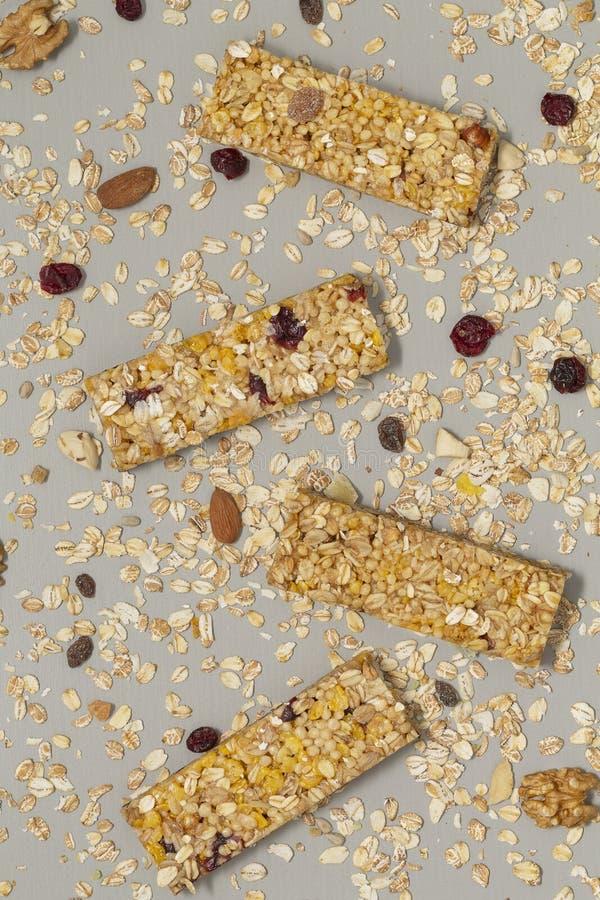 De staaf van Granola De bar van graangewassengranola met noten, fruit en bessen op een grijze steenlijst Gezonde zoete dessertsna stock foto's
