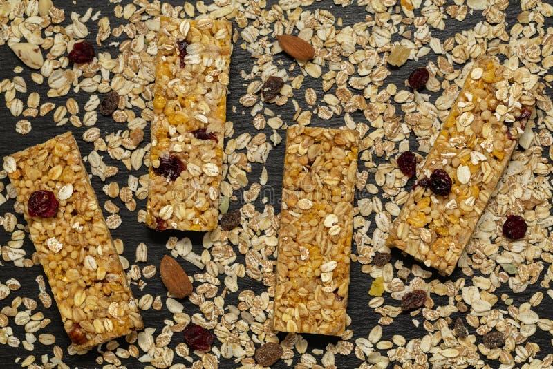 De staaf van Granola Gezonde zoete dessertsnack De bar van graangewassengranola met noten, fruit en bessen op een zwarte steenlij stock afbeelding
