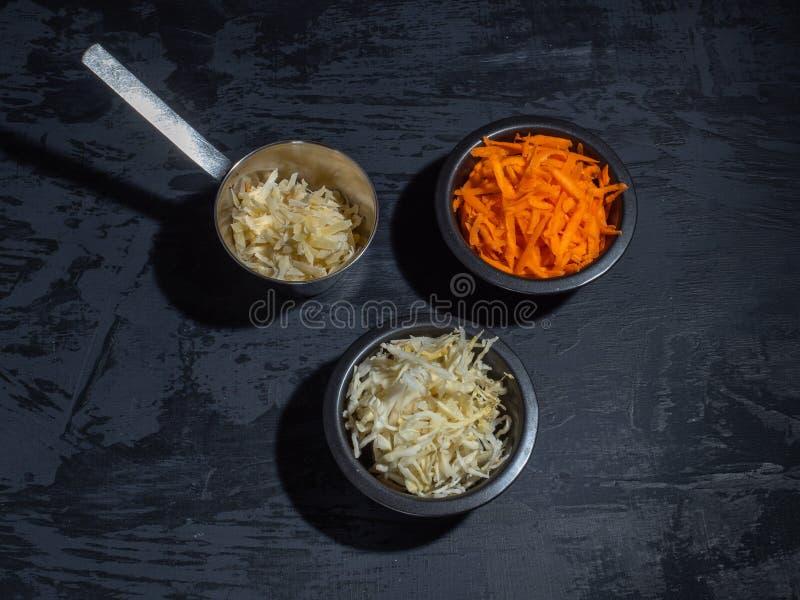 De staaf voor salade, gesneden wortelkool in zwarte platen, raspte kaas stock fotografie