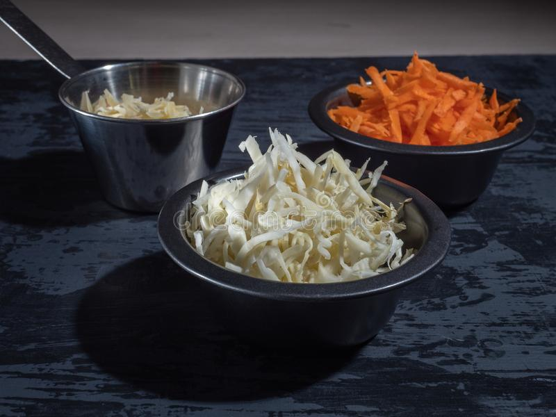 De staaf voor salade, gesneden wortelkool in zwarte platen, raspte kaas royalty-vrije stock afbeelding