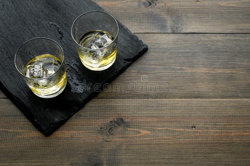 In de staaf Whisky met ijs op zwart bureau op houten achtergrond hoogste meningsruimte voor tekst stock afbeeldingen