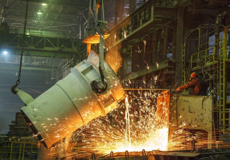 De staalarbeider neemt een steekproef van heet metaal stock foto's